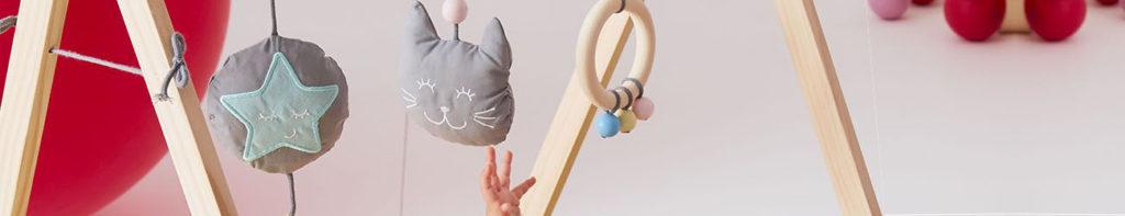 Un bébé joue avec son arche en bois. Il cherche à attraper les formes suspendues.