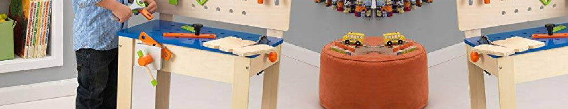 Un enfant joue avec son etabli en bois pour enfant. Il tient un outil et est prêt à réparer une pièce.